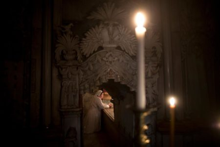 """A Christian nun kneels in prayer at the """"burial bed"""" of Christ inside the tomb shrine, known as the Edicule. PHOTOGRAPH BY ODED BALILTY, AP FOR NATIONAL GEOGRAPHIC"""